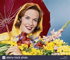 1960s smiling woman under red umbrella yellow raincoat holding