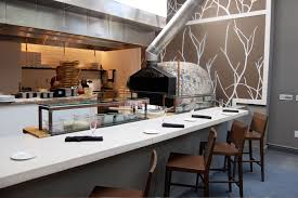 Near The Restaurant Entrance A Four Seat Dining Counter Faces An Open Kitchen And