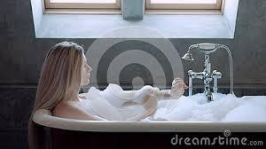 schöne blondine liegt in einem bad mit schaum und relax