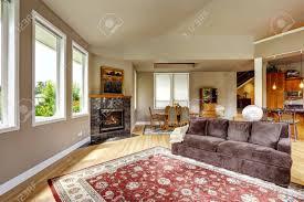 geräumiges wohnzimmer mit hohen gewölbten decke und parkett granit hintergrund kamin und roten teppich