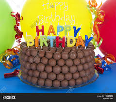 Chocolate cake decorated with rows of malt balls with happy birthday candles bright balloons