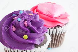 Two chocolate cupcakes one with purple frosting the other in pink Stock