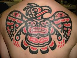 A Tribal Tattoo Of An Aztec Eagle With Grinning Face And Eye Designs
