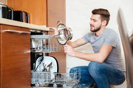 Man Inspecting Clean Dishes From Dishwasher On Water Softener System