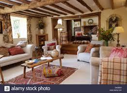 weiße sofas und sessel mit rustikaler couchtisch aus holz in