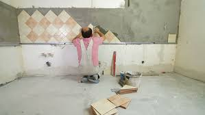 worker installing tiles to a kitchen wall wide angle stock