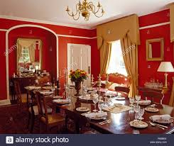 Long Table Set For Lunch In A Red Country Dining Room With Cream Silk Drapes And Pelmet