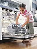Girl Unloading Dishwasher Low Angle View Stock Photo