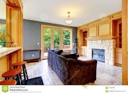 wohnzimmer mit blauen wänden kamin und braunem sofa
