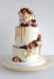 A Three Tiered White Wedding Cake Dripping With Caramel Rustic Fall Fruits And