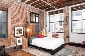 Rustic Brick Loft Bedroom With Wood Flooring And Exposed Beam Ceiling