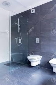 luxuriöse grau badezimmer mit großen granit fliesen auf dem boden und wände und glasduschwand