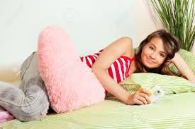 smiling teenage texting from her cell phone laying in bed