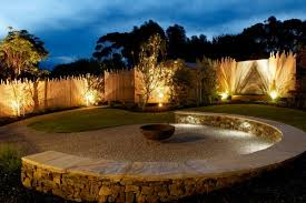 This Curved Half Wall Is Lined With Path Lighting While The Walls Around Yard Have