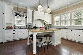 Country Kitchen With White Shaker Cabinets Butcher Block Island And Black Granite Countertops