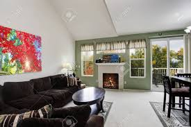 wohnzimmer mit kontrastoliven wand und gewölbe hohen decke mit braunen möbeln eingerichtet ansicht der ausstand deck