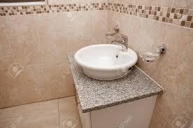 ein weißer rundbecken auf einem weißen granit positioniert gekrönt schrank in einem bad bauen die mit hellbraunen fliesen oben nach unten in