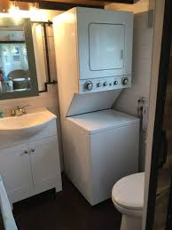 A Stackable Washer And Dryer Unit Is Tucked Into The Corner Next To Full Sized Toilet When You Need Privacy Just Slide Barn Door Between