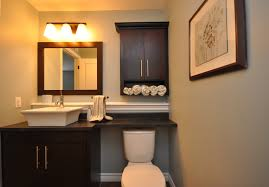 Black Wall Mounted Bathroom Storage Cabinet With Towel Shelves Over Toilet Beside Wooden Under Mirror And Lighting Ideas