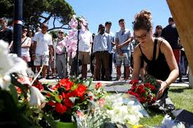 A Woman Places Bouquet Of Flowers As People Pay Tribute Near The Scene Where