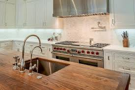butcher block island top with stainless steel sink and two faucets