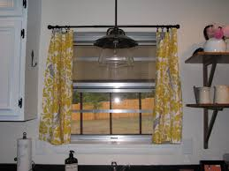 small kitchen window with yellow and gray ring top curtain