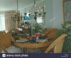 Wrought Iron Chandelier Above Wicker Table And Chairs In ...