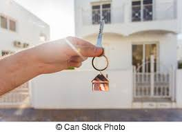 Holding House Keys On Shaped Keychain Closeup In Front Of A New Home Concept