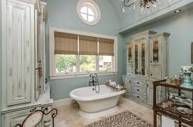 Bathroom French Country Woth Small Oval White Bathtub Also Grey Rustic Wood Cabinet And Brown Floral Pattern Fabric Rug Under Clear Crystal