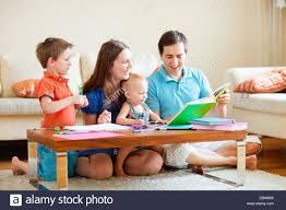 familie mit zwei kindern lesen und malen im wohnzimmer