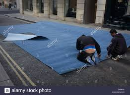 A Team Of Asian Men Measure And Cut Roll Industrial Carpet In Side Street Destined For Nearby Shop Londons New Bond