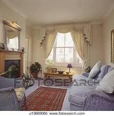 swagged und tailed creme vorhänge in wohnzimmer mit