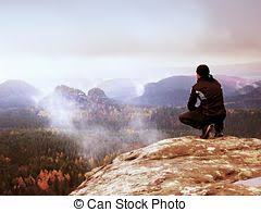 Tourist In Black Sit On Cliffs Edge Looking To Misty Hilly Valley