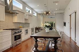 Contemporary One Wall Kitchen With White Cabinets Wood Floors And Dining Table