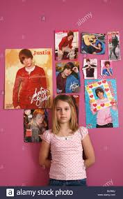 An 11 Year Old Girl Standing In Front Of A Wall Full Justin Bieber Posters
