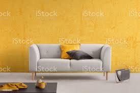gelbe textur an der wand des eleganten wohnzimmer mit stilvollen sofa mit kissen echtes foto mit textfreiraum stockfoto und mehr bilder behaglich