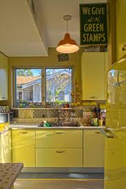 Vinatge 50s Kitchen Decor With Yellow Refrigerator And Wooden Cabinet Also Two Small Windows