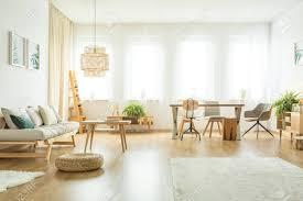 puff neben beige sofa mit kissen im hellen wohnzimmer interieur mit tischen stühlen und farnen