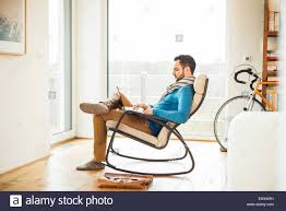 Young Man Sitting On Rocking Chair Using Laptop Stock Photo ... Rocking Chair For Nturing And The Nursery Gary Weeks Coral Coast Norwood Inoutdoor Horizontal Slat Back Product Review Video Fort Lauderdale Airport Has Rocking Chairs To Sit Watch Young Man Sitting On Chair Using Laptop Stock Photo Tips Choosing A Glider Or Lumat Bago Chairs With Inlay Antesala Round Elderly In By Window Reading D2400_140 Art 115 Journals Sad Senior Woman Glasses Vintage Childs Sugar Barrel Album Imgur Gaia Serena Oat Amazoncom Stool Comfortable Cushion