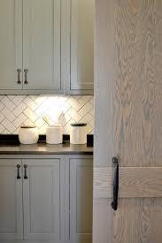 white herringbone backsplash tiles with black grout transitional