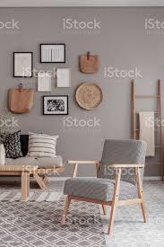vintage sessel mit kariertem muster neben bequemen beige sofa mit kissen in schönen wohnzimmer interieur stockfoto und mehr bilder behaglich