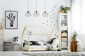 moderne baby schlafzimmer in weiß mit bett bücherregal und teppich