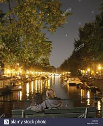 100 Brouwer Amsterdam Rear View Of Couple Sitting On Bench In Evening In Front Of