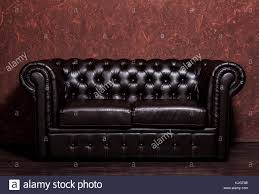 jahrgang alte dunkelbraun leder sofa mit grunge braun wand