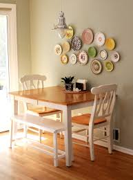 table against the wall two chairs one bench seat seating for