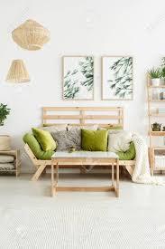 poster mit pflanzen hängen an der weißen wand im stilvollen wohnzimmer interieur mit grünen sprinkler und holztisch