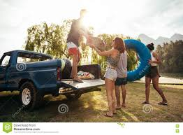 Young Friends Unloading Pickup Truck On Camping Trip Stock Image ...