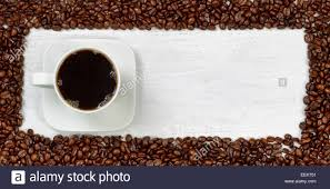 Top View Angle Of Freshly Made Dark Coffee With Roasted Beans Forming Even Border On White Wooden Table
