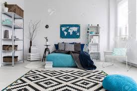 große schlafzimmer interieur in weiß angeordnet und blau mit bequemen bett gefüllt mit kissen schwarzen und weißen teppich und holzkastenmöbel
