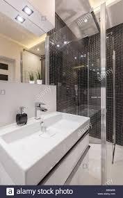 badezimmer mit weißen waschbecken spiegel und schwarz